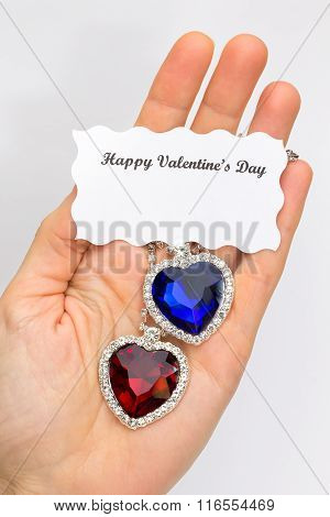 Hand Showing Red And Blue Jewelry Hearts For Valentine