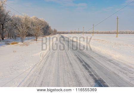 Winter landscape with country road covered by ice in central Ukraine