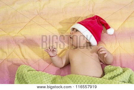 Portrait Of A Newborn Baby Boy With Santa's Hat In Bed