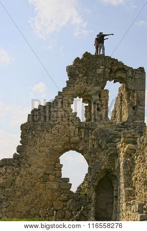 Two Traveler Stand On Top Of The Ancient Ruins And Point Hand Away. The Guide Shows The Travel Agenc