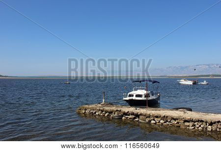 Mediterranian seaside view with small handmade pier and boats