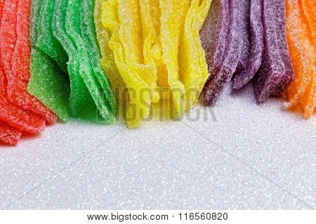 Colorful sugar jelly candy strip over white background