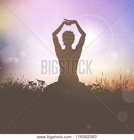 Silhouette of a female in a yoga pose against a sunset sky