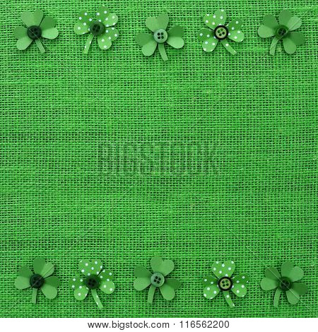 St Patricks Day frame of paper shamrocks on green burlap
