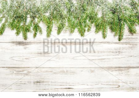 Christmas Tree Sprigs With Snow On Wooden Background