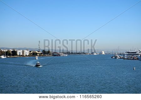 Boats Motor Through Oakland Harbor On A Clear But Hazy Day