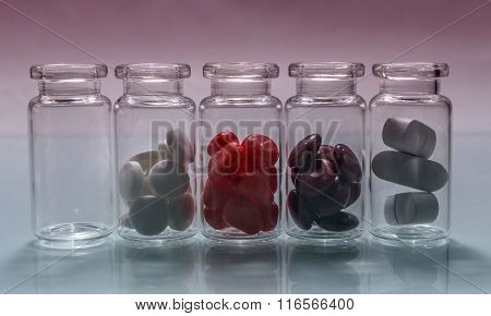 Small Bottles Of Diferent Pills Lined Up