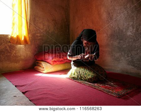 A female physically-handicapped facial-cancer sufferer in her forties reads the Koran (Al Qur'an)
