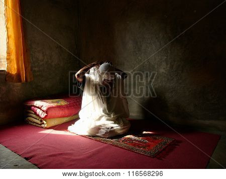 A female physically disabled Muslim facial-cancer sufferer performs Islamic midday prayers alone