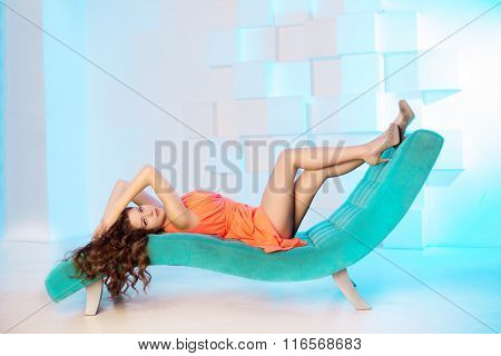 Sexy woman lying on sofa in luxury interior. Sexy beautiful girl with long legs in bed, beauty hair.