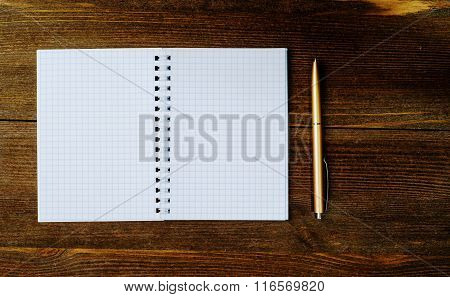 Pen And Notepad Placed On A Wooden Background.
