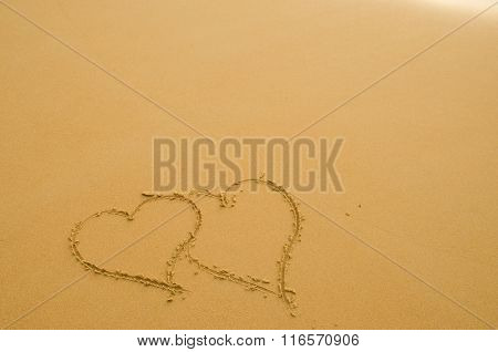 Drawing a heart on the white sand beach