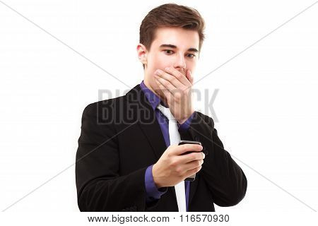 Young Businessman Fearfully Looking At The Phone And Covers His Mouth