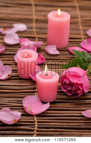Pink rose with candle and petals on mat