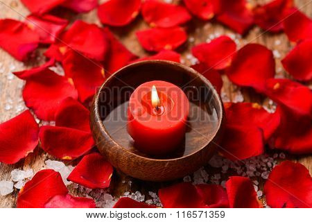 Candle in bowl Roses petals with pile of salt on old wooden board