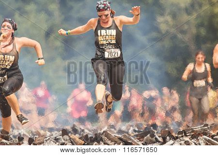 Woman Hurdles Burning Logs In Extreme Obstacle Course Race