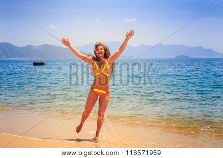 Blonde Slim Girl In Bikini Poses Hands Over Head On Beach