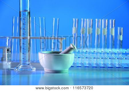 Laboratory mortar with glassware on table