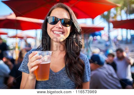 woman with plastic cup of beer at outdoor bar or pub