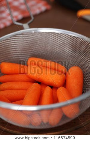 Pealed mini carrot in a strainer