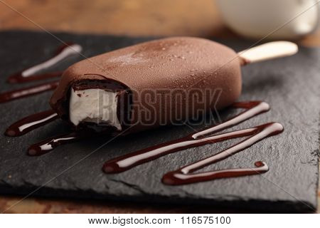 Ice cream bar coated with chocolate on a slate board
