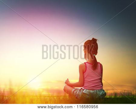 Child girl in the Park. Yoga at sunset in the park. Girl is practicing yoga.