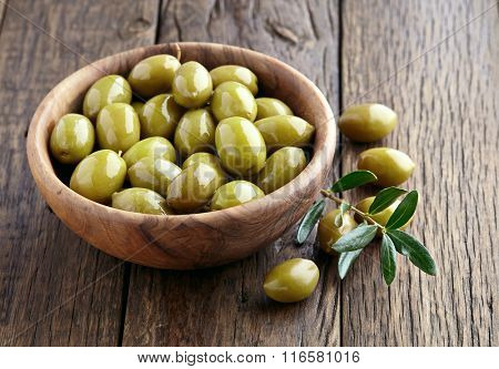 Green olives on a wooden background