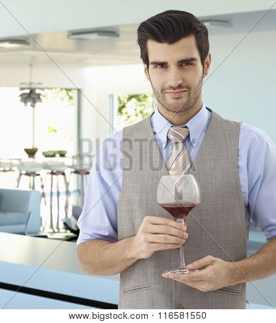 Charming handsome young caucasian man with glass of wine in hand standing indoors. Wearing suit and tie, smiling, looking at camera.