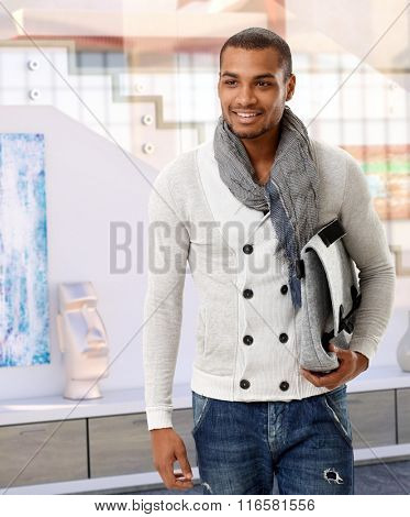 Happy casual trendy handsome arabian man with handbag at classy gallery. Standing, smiling.