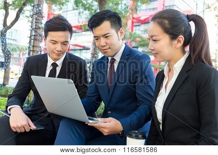 Group of business people look at the laptop computer