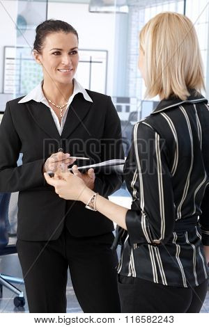 Elegant businesswoman discussing business at office.