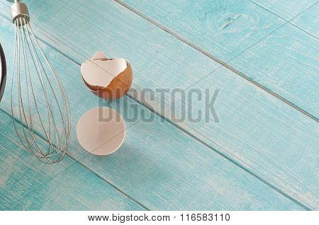 Eggshell With A Whisk On A Blue Kitchen Table Closeup