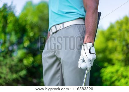 Man with ball and club outdoors