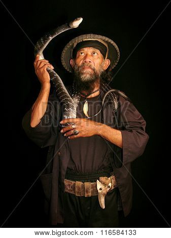 Member of an Indonesian sideshow performs with a live snake