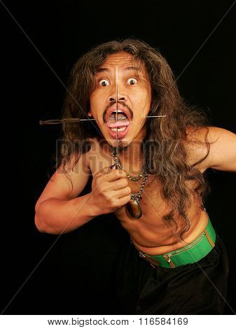 Member of an Indonesian sideshow pierces his face with skewers