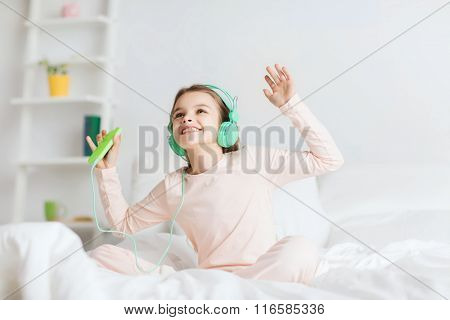 girl sitting on bed with smartphone and headphones