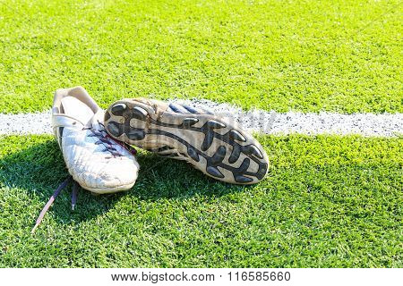 Old football shoes on green grass filed