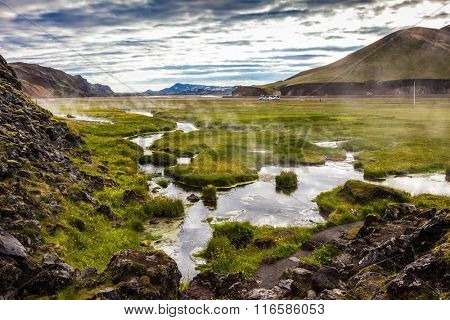 Hot steam over the source of the thermal waters. Sunrise Park Landmannalaugar. White nights in Iceland