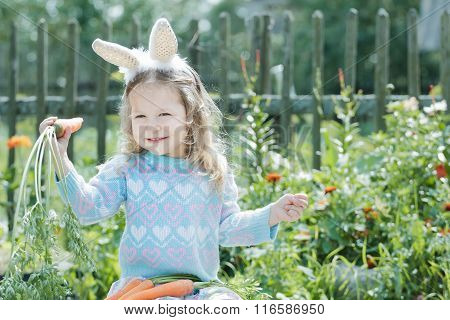 Portrait of smiling preschooler blonde girl with Easter bunny DIY ears and fresh carrots
