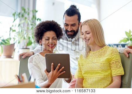 happy creative team with tablet pc in office