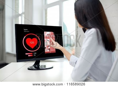 close up of woman with heart pulse on computer
