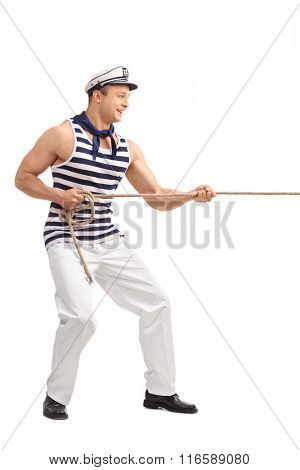 Full length profile shot of a young male sailor pulling a rope isolated on white background