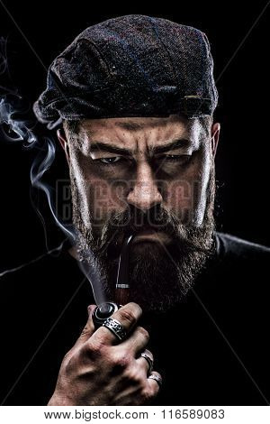 Vertical shot of an angry man with a thick beard smoking a pipe and looking at the camera on black background