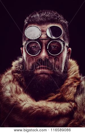 Portrait of a man in a fur coat wearing goggles and looking at the camera on dark background