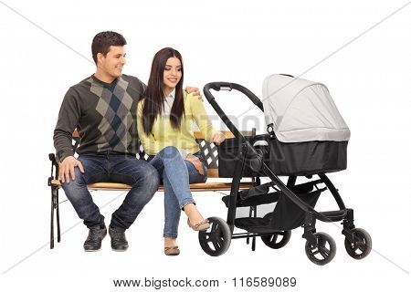 Studio shot of a young parents sitting on a wooden bench with a baby stroller beside them isolated on white background