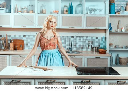 Blonde Girl Standing In The Kitchen Next To Stove.