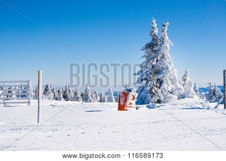 Vacation rural winter background with white pine, fence, snow field, mountains