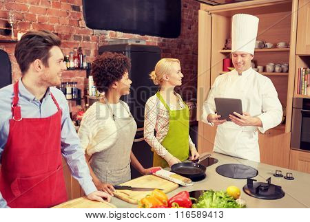 happy friends with tablet pc in kitchen