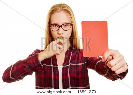Woman with whistle showing a red card after a foul