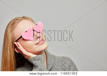 Young woman daydreaming with hearts on her eyes looking up